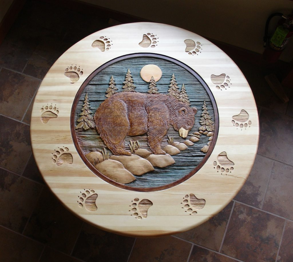 A wooden tabletop with a bear carved into it.