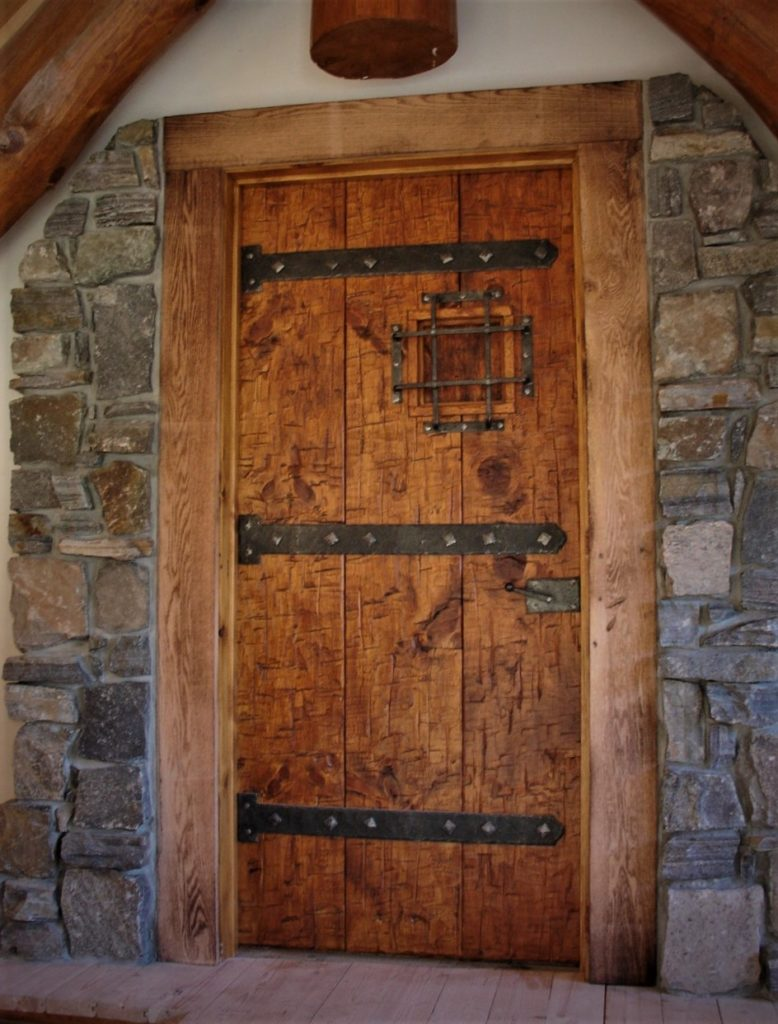 A heavily distressed door with straps.