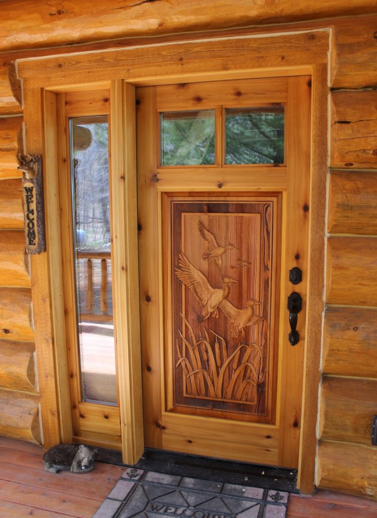 A wood door with ducks carved into it.