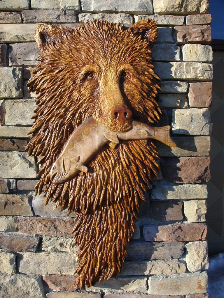 A wooden plaque of a bear with a fish in its mouth.