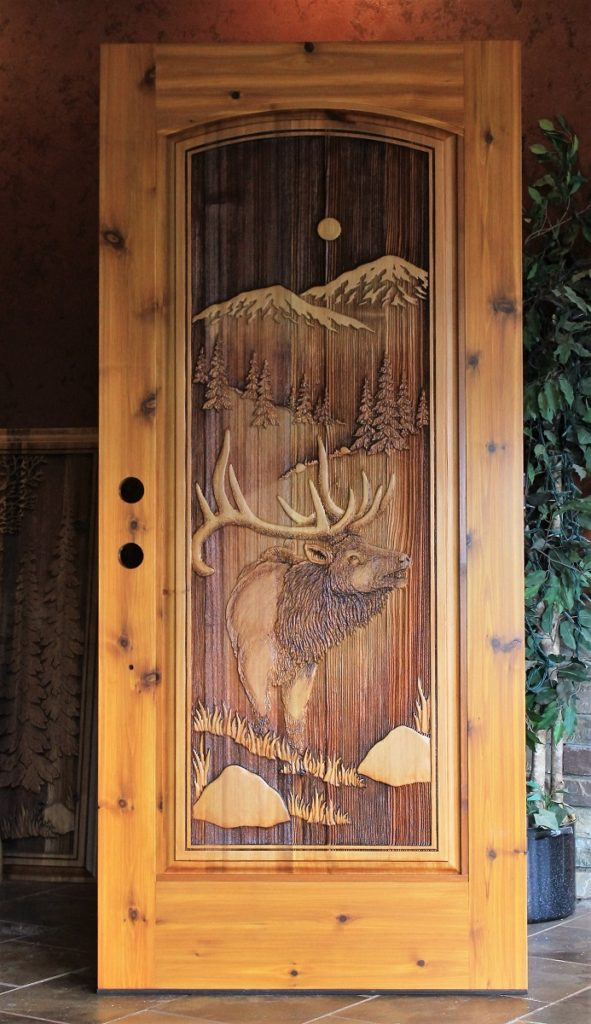 A wood door with an elk carved into it.